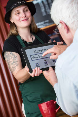 finger tip: Man pays cafe bill and tip by signing with finger for credit card on a tablet Stock Photo