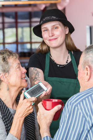 Customer giving barista her phone with barcode coupon on it