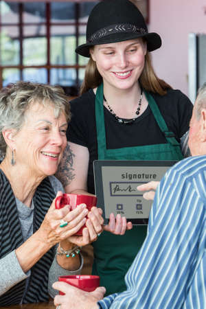 gratuity: Senior signs name on a tablet to pay bill in coffee house Stock Photo