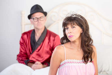 jeweled: Retro style snooty playboy and pretty bored woman with jeweled tiara on white bed