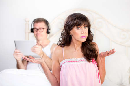 distracted: Upset woman and distracted man in bedroom