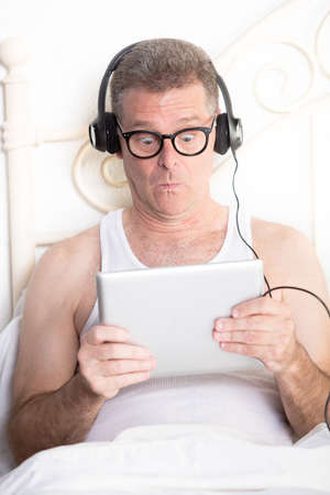 Man in bedroom reacting to content on computer tablet