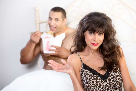 Beautiful mature woman with handsome younger man eating Chinese food in bed Stock Photo
