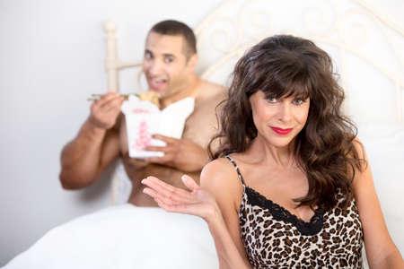 Mooie rijpe vrouw met knappe jonge man het eten van Chinees eten in bed