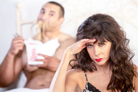 uncouth: Beautiful mature woman with handsome younger man sloppily eating Chinese food in bed