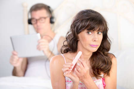 ignore: Bored woman and distracted man using tablet computer with headphones in bedroom Stock Photo