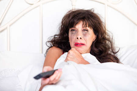 Mature woman in bed watching something sad on television