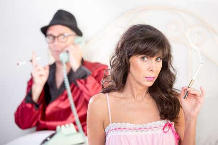 uomo rosso: Il fumo stile retrò playboy snooty sul telefono matura bella donna