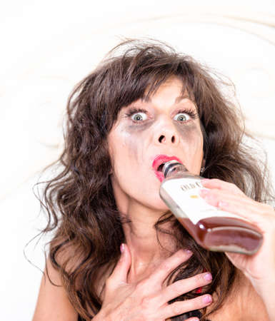 Mature drunk woman drinking whiskey from a bottle in bedroom Stock Photo