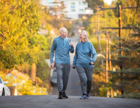 couple exercising: Active man gesturing while talking to cheerful woman on street