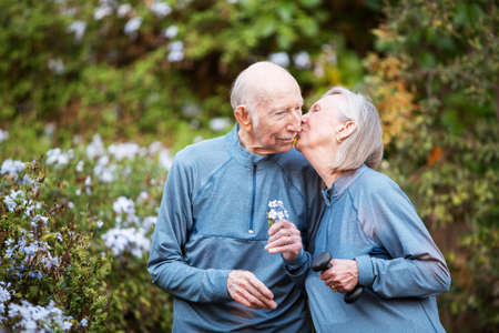 smooching: Loving senior couple kissing each other outside in front of garden