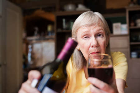 First person perspective of drunk senior woman offering wine and full glass