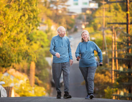 stride: Enthusiastic man and woman with dumbbell weights walking up hill on street