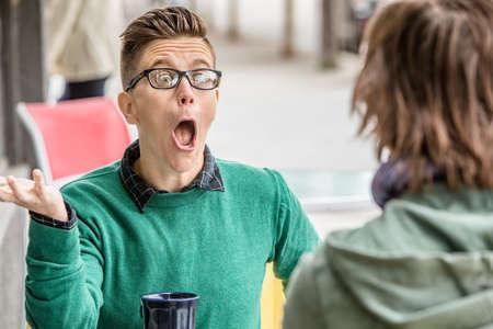 Yelling Frau im grünen Pullover mit nicht identifizierbaren Freund sprechen im Restaurant unter freiem Himmel