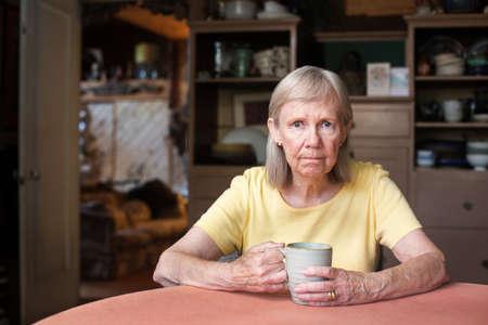 molesto: mujer mayor sola frustrada en la taza amarilla camisa de retención mientras se está sentado en la mesa