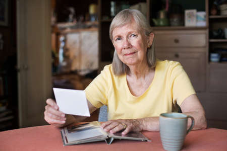 senior woman: Proud senior woman hold photo from picture album while seated near coffee cup