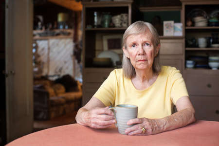 uneasy: Senior woman in yellow shirt with depressed expression holding cup indoors