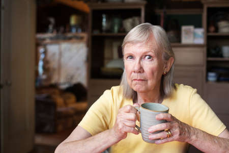 Single mature woman with angry expression holding cup while seated at table Stock Photo