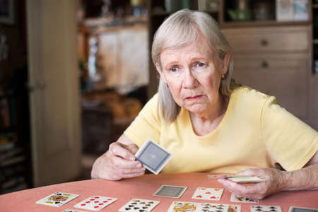 Woman playing a card game with worried or losing expression