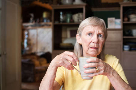 Worried lonely senior woman in yellow shirt holding coffee cup indoors