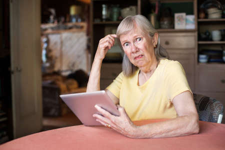 Single older female adult with confused expression holding tablet computer