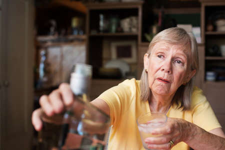 tipsy: Lonely senior adult female reaching for a bottle of liquor while holding a glass