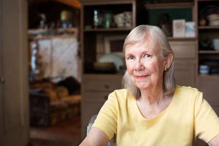 flattered: Grinning confident senior adult female in yellow shirt indoors