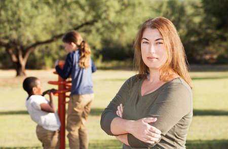 madre soltera: madre soltera de pie delante de dos niños jugando detrás de ella
