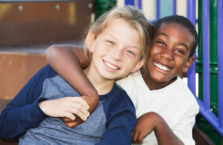Happy African and Caucasian male child friends on playground set Stock Photo