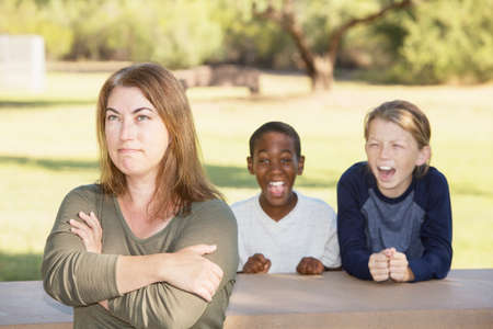 irked: Frustrated mother sitting with loud sons demanding something outside
