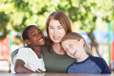 Joyful single parent sitting in between adopted child and son at table in park Foto de archivo