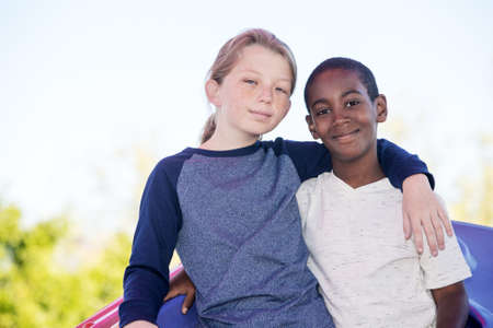 fostering: Calm cheerful boy with cute adopted brother embracing outside Stock Photo