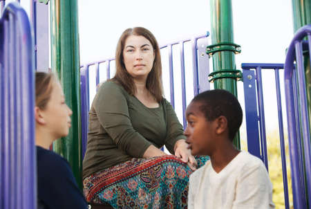 fostering: Two children talking to each other on playground set with mother watching from behind them Stock Photo