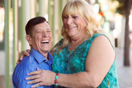 Laughing transgender couple embracing each other while outside in urban setting
