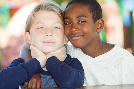 fostering: Pair of adopted brothers sitting close to each other outside