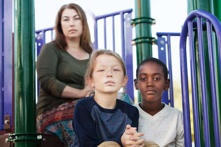 Two male children sitting on playground set with mother behind them Imagens