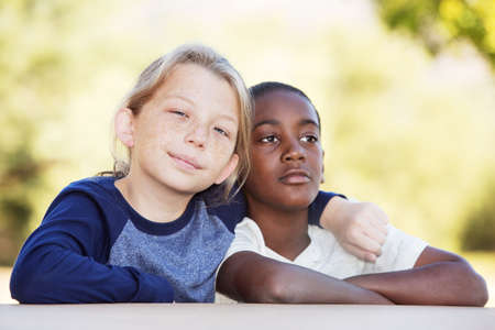 fostering: Pair of adopted brothers sitting beside each other outside Stock Photo