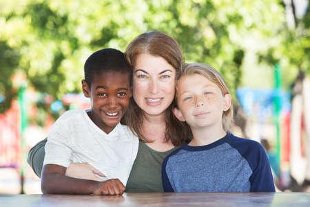 Moeder knuffelen en zitten in tussen adoptiekind en zoon aan tafel in het park