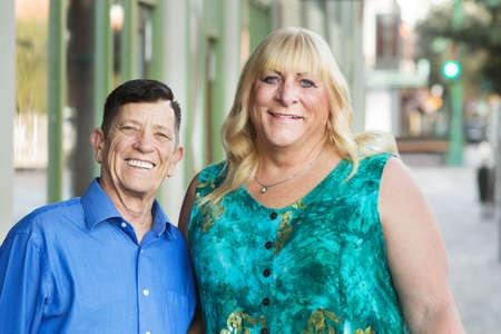 Lachende oudere transgender vrienden staan samen buiten in de stedelijke omgeving