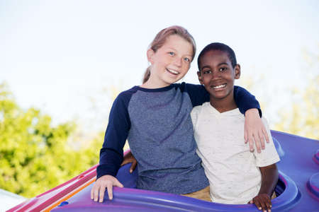 fostering: Laughing cheerful boy with cute adopted brother embracing outside Stock Photo