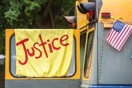 yellow schoolbus: Yellow justice banner with American flag hanging from side of old school bus