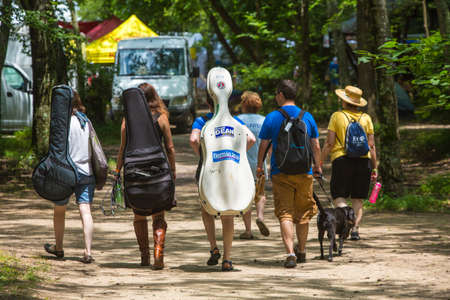 HOT SPRINGS, NC - JULY 8: Rear view of musicians walking with their string instrument cases as the Wild Goose Festival on July 8, 2016 in Hot Springs, NC, USA. Editorial