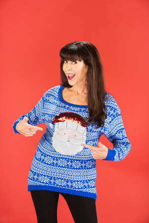Happy single woman pointing to her ugly blue sweater with Santa Claus face on it 版權商用圖片