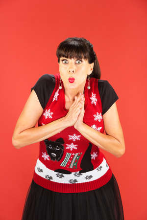 puckered lips: Front view on single woman in garish Christmas sweater with palms together over red background Stock Photo