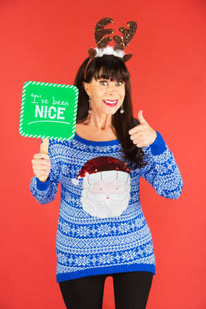 Happy single woman in antlers tiara holding nice sign over red background