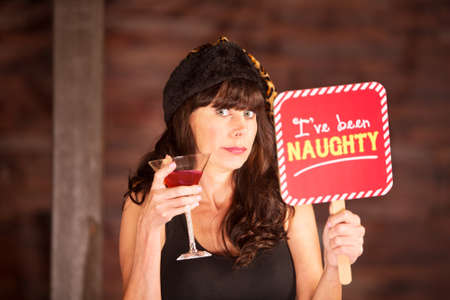 boasting: Cute woman in leopard skin hat caught being naughty while holding sign and martini in other hand