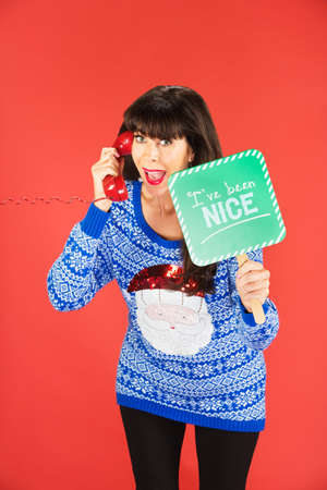 Excited woman in ugly blue Santa sweater holding green nice sign while on phone