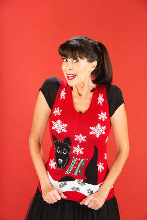 Front view on excited single woman showing off her ugly Christmas theme sweater over red background Imagens - 69218511