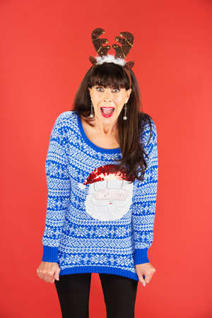 flattered: Excited beautiful single woman in blue sweater and antlers tiara over red background