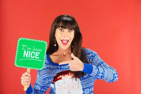 Happy single woman in ugly knitted sweater pointing to nice sign over red background Imagens - 69218514